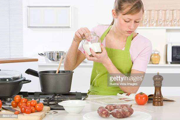 woman cooking in kitchen, reading recipe