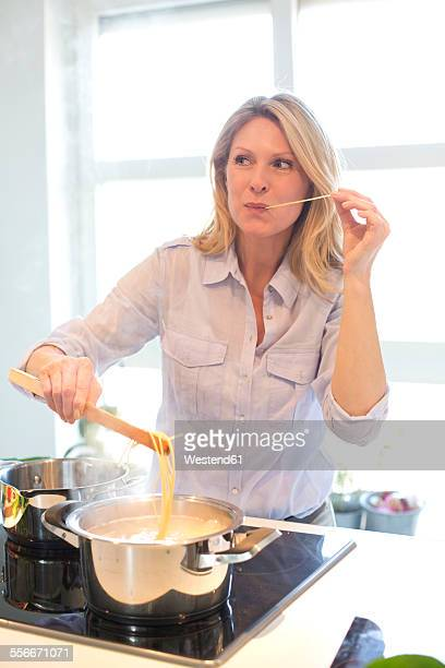 Woman cooking in kitchen tasting spaghetti