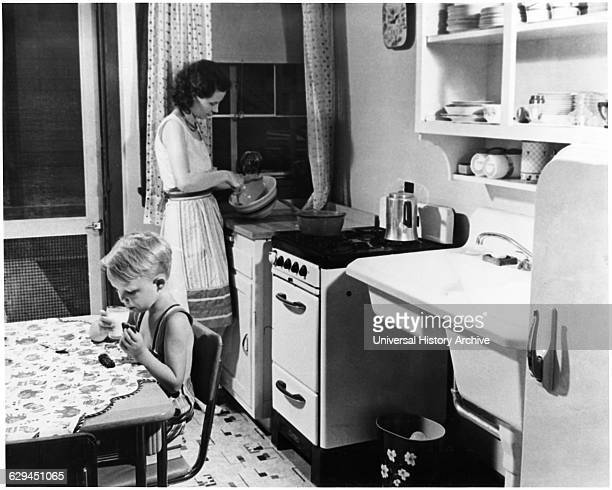 Woman Cooking in Kitchen with Young Boy Eating Cookies with Milk USA circa 1955 from the Documentary Film 'Emerging Woman' Women's Film Project 1974