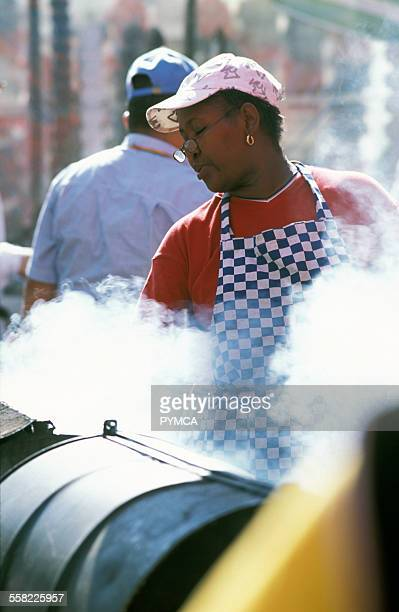 A woman cooking on a barbecue Notting Hill Carnival London UK 2006