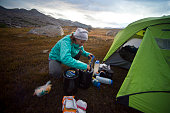 Woman cooking outside her tent in the Sierra mountains