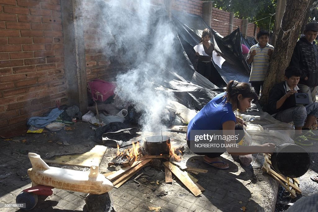 A woman cooks in an encampment of natives of the Mbya ethnic group set in front of the Paraguayan Institute for the Natives (INDI) in Asuncion on May 31, 2016. The Mba are camped since 30 days ago demanding to the government to be granted the ownership of the 500 hectares of land they live in. / AFP / NORBERTO