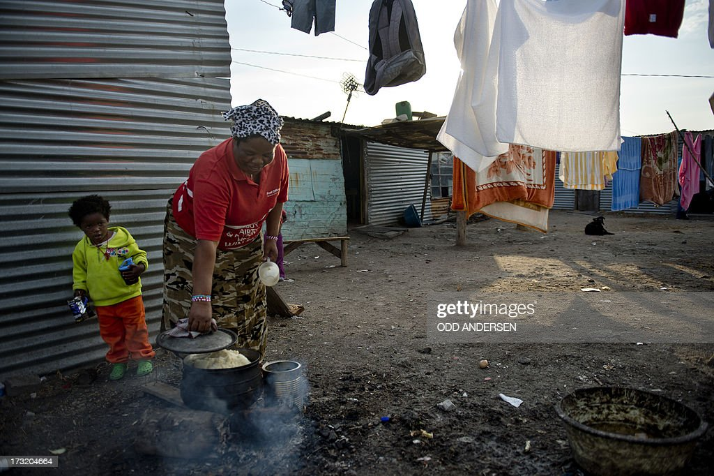 A woman cooks on July 9, 2013 in the Nkaneng shantytown next to the platinum mine, run by British company Lonmin, in Marikana. On August 16, 2012, police at the Marikana mine open fire on striking workers, killing 34 and injuring 78, during a strike was for better wages and living conditions. Miners still live in dire conditions despite a small wage increase.