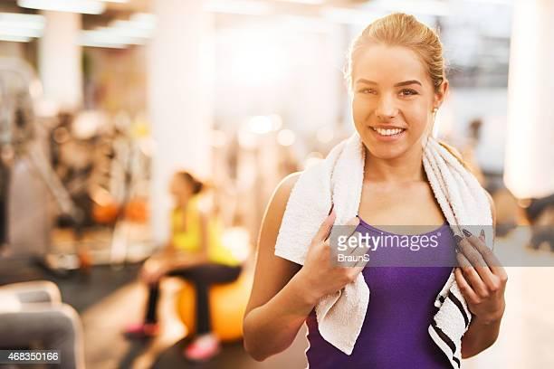 Mulher feliz tendo uma pausa de exercitar no Clube de Saúde.