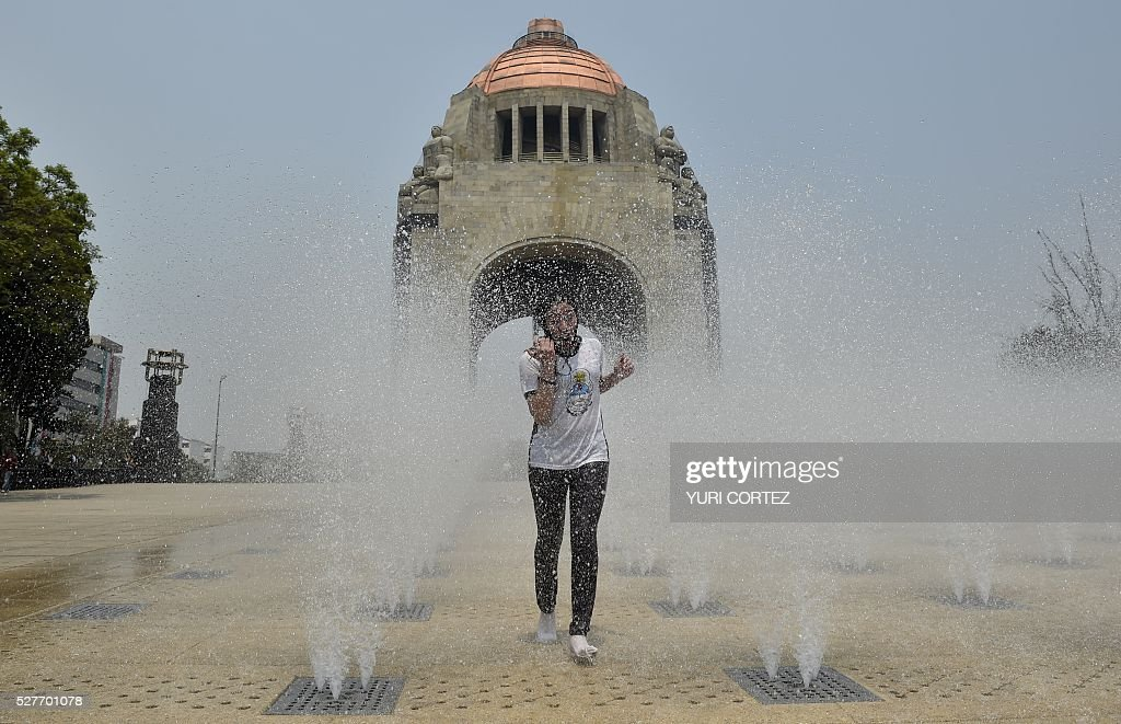 A woman cools herself down in a water fountain at the Revolution square during a heat wave in smog-covered Mexico City on May 3, 2016. Mexico City officials issued a new air pollution alert yesterday, meaning that 40 percent of vehicles will be banned on Tuesday, while industries will be required to cut emissions. The alarm was raised after ozone levels reached 161 points, above the 150 level. The threshold was lowered from 190 to 150 last month. / AFP / YURI