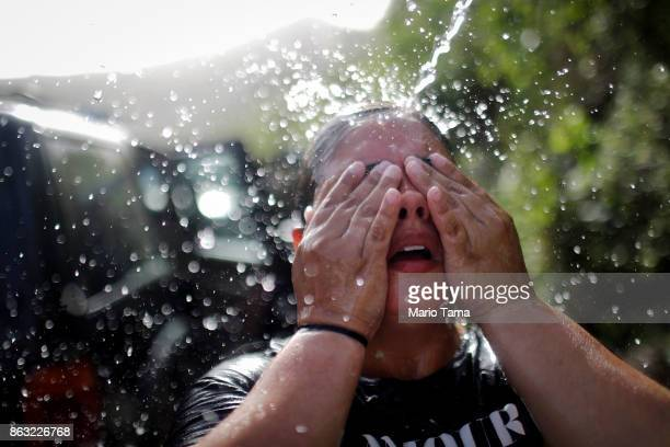A woman cools off with water funneled with pipes from a mountain spring after filling jugs of water for her home nearly one month after Hurricane...