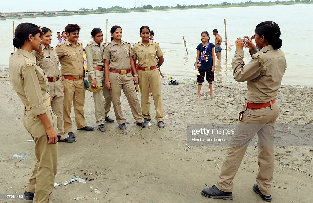 A woman cop clicks picture of her colleagues at the Saryu Ghat as normalcy returned on August 26, 2013 in Ayodhya, India. High security was on alert in Ayodhya in wake of Vishwa Hindu Parishad's (VHP) 84 Kosi yatra, which was banned by Uttar Pradesh government.