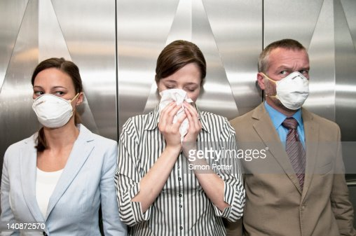 Woman coughing around others in elevator