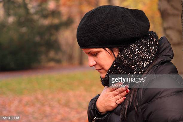 Woman coughing in autumn.