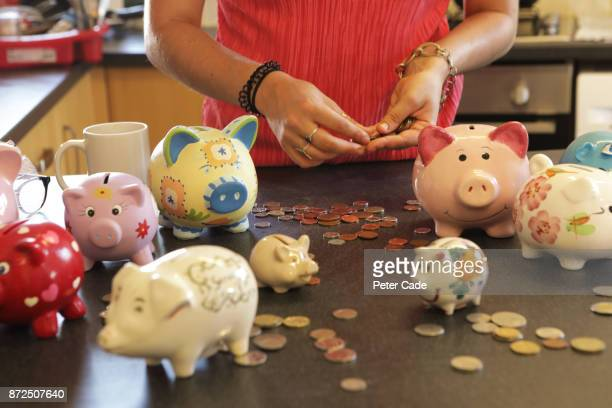 Woman counting change from piggy banks