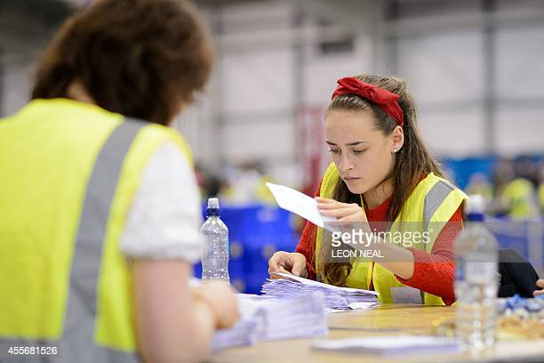 A woman counts ballots at the Royal Highland Centre counting hall in Edinburgh Scotland on September 19 after ballot counting got underway in the...