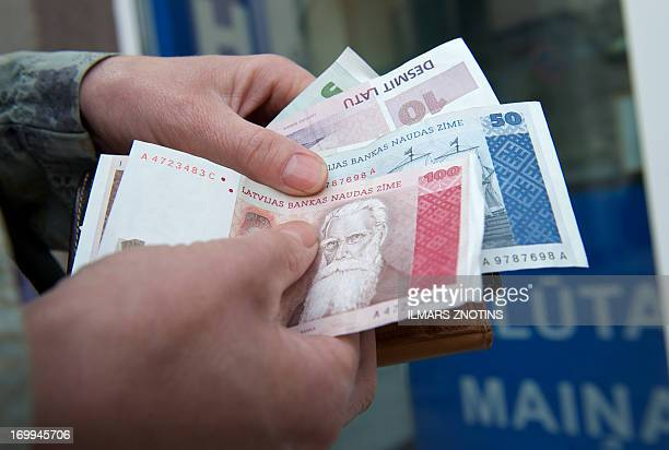 A woman counts her Latvian lats at a currency exchange office in Riga on June 5 2013 Unfazed by the eurozone's lumbering debt crisis Latvia an...