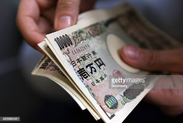 A woman counts Japanese 10000 yen notes in this arranged photograph taken in Tokyo Japan on Friday Dec 13 2013 The yen fell to a fiveyear low versus...
