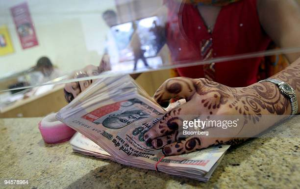 A woman counts rupee notes at a cash counter of a bank in Mumbai India on Tuesday May 29 2007 India's economic growth unexpectedly quickened last...