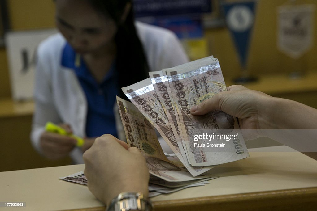 A woman counts Thai bhat before depositing at a local bank on August 23, 2013 in Bangkok, Thailand. The local currency dropped to its lowest level since August 2010. Against the US dollar the Thai baht fell to 32.09/32.13 dropping about 5% this year.