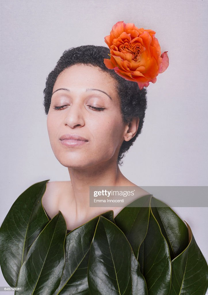 Woman covered by large leaves