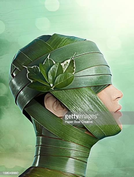 woman covered in a mask made of leaves