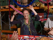 Woman covered in party streamers laughing at charismas table in warehouse