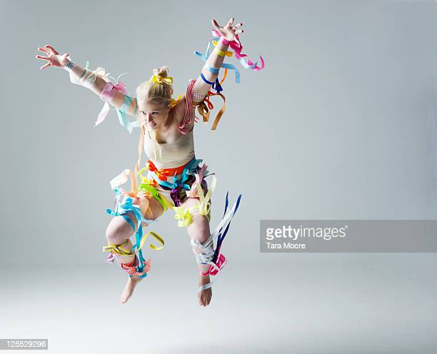 woman covered in ribbons jumping in studio