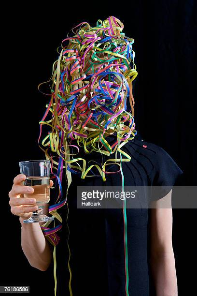 A woman covered in streamers and holding a glass of champagne