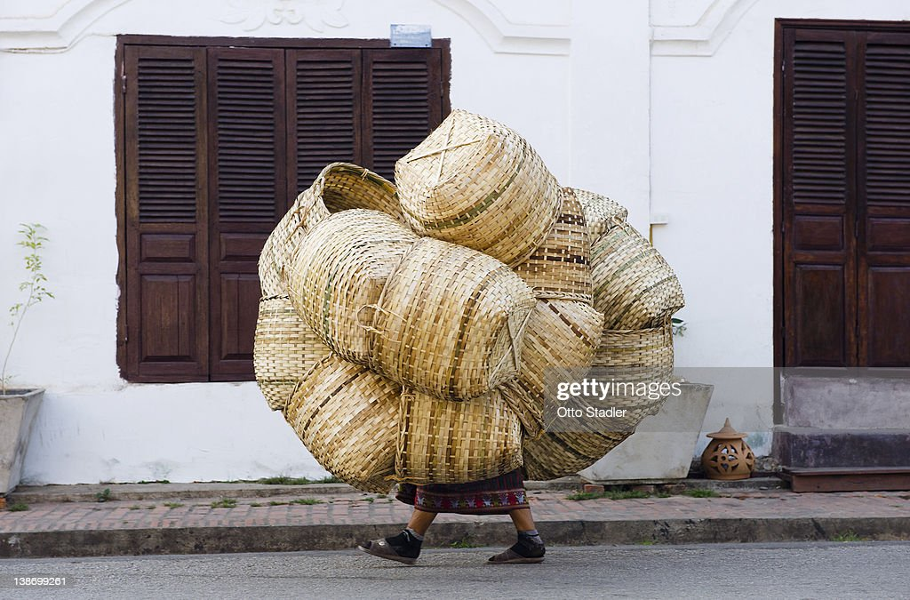 Woman covered with baskets on the way to market : Stock Photo