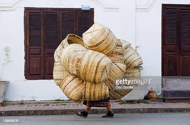 Woman covered with baskets on the way to market