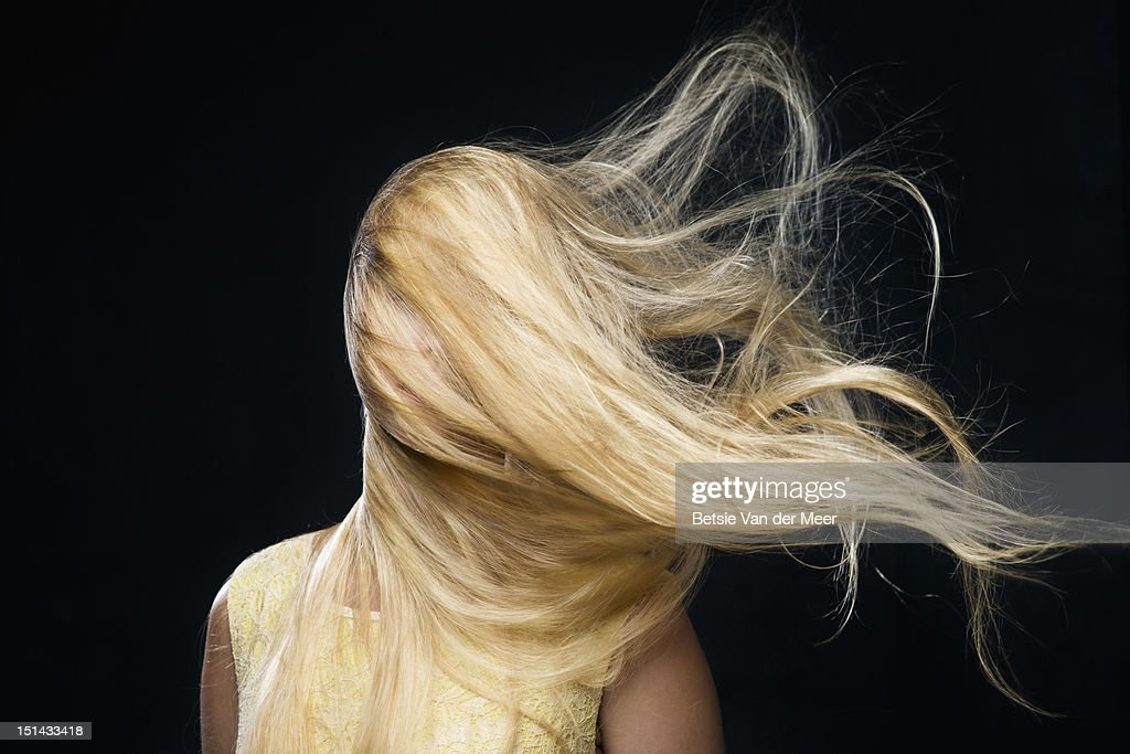 woman covered with blowing hair in wind.