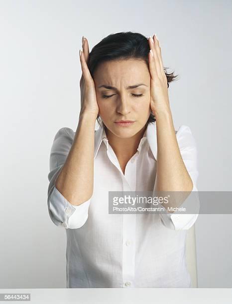 Woman covering ears, portrait