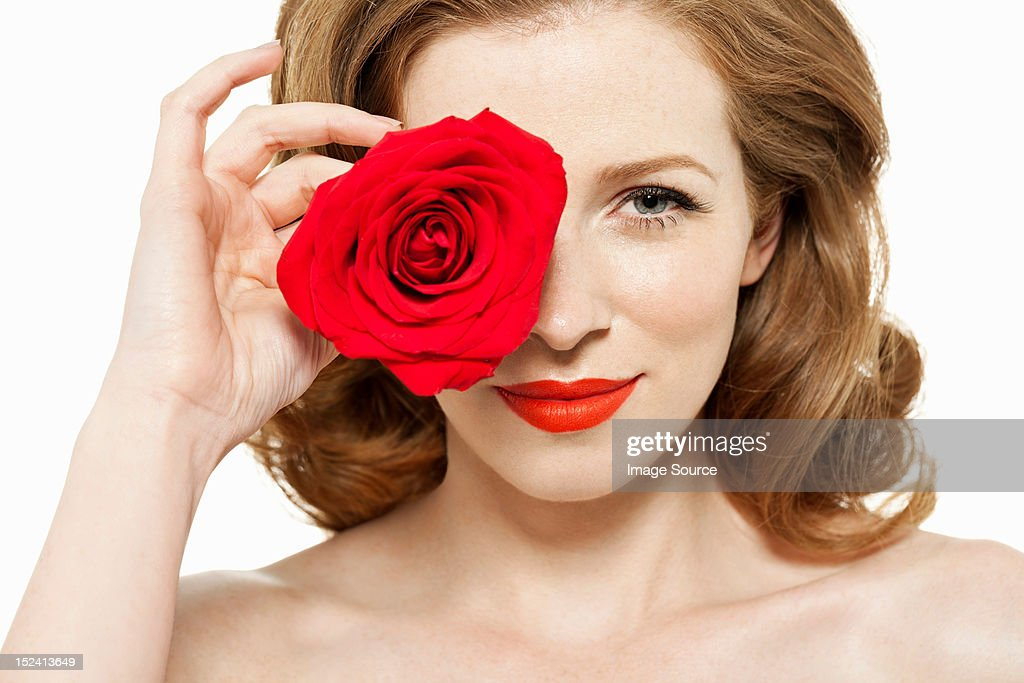 Woman covering eye with red rose : Stock Photo