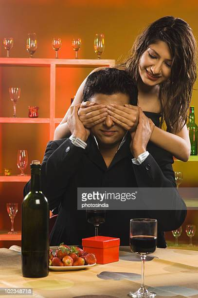 Woman covering eyes of her boyfriend in a bar