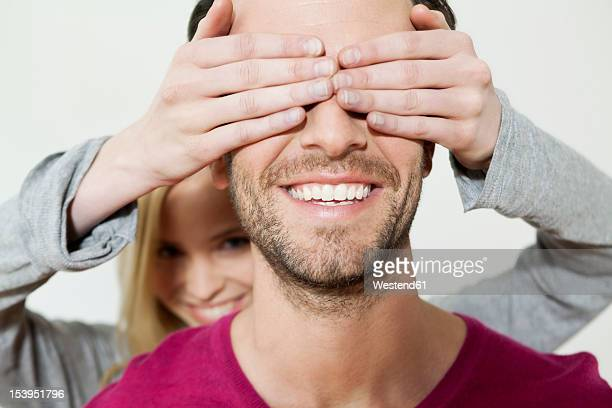 Woman covering eyes of man, smiling, close up
