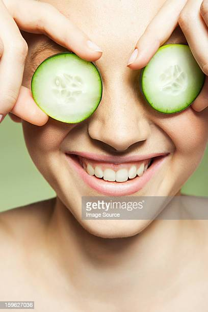 Woman covering eyes with cucumber