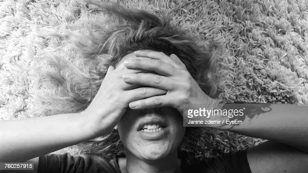 Woman Covering Eyes With Hands While Lying On Rug At Home