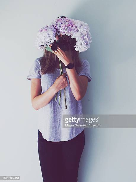 Woman Covering Face With Flowers Against White Background