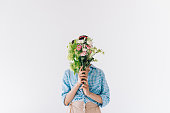 obscured view of woman covering face with bouquet of flowers isolated on grey