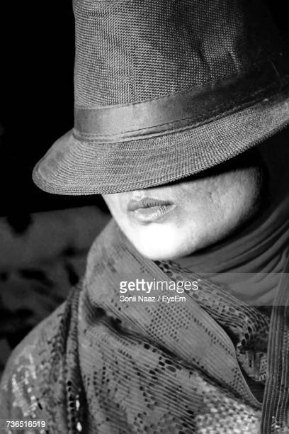 Woman Covering Face With Hat At Home