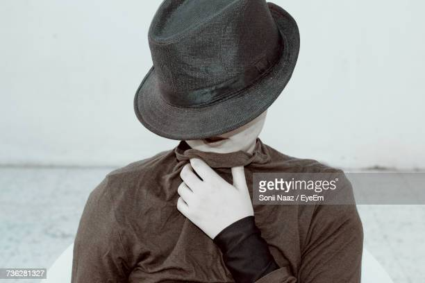 Woman Covering Face With Hat While Standing Against Wall