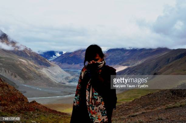 Woman Covering Face With Scarf While Standing Against Mountains