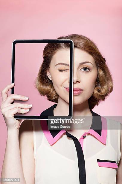 Woman covering half her face with digital tablet