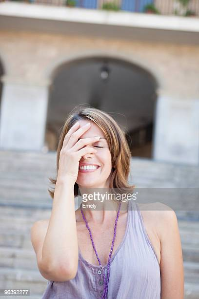 woman covering her eyes smiling