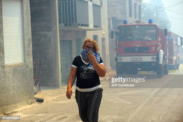A woman covering her face with a cloth walks through the streets during a fire in the village of Gornje Sitno near the Adriatic coastal town of Split...
