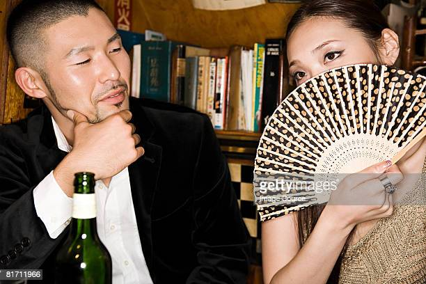 Woman covering her face with a hand fan