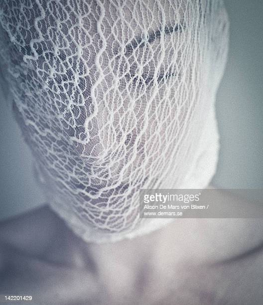 Woman covering her face with white lace