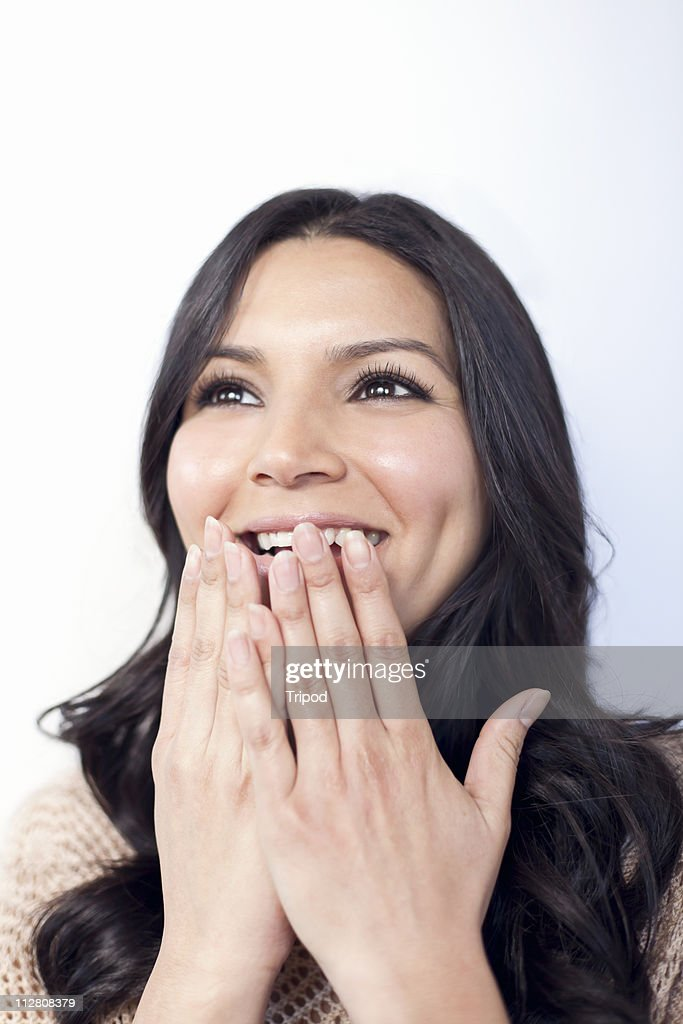 Woman covering mouth with hands, close-up : Stock Photo