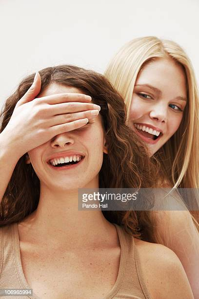 Woman covering woman's eyes and laughing