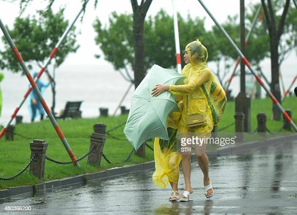 A woman covers her child with an umbrella amid a heavy storm brought by typhoon Chanhom in Hangzhou east China's Zhejiang province on July 11 2015...