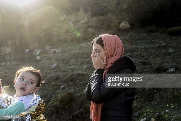 A woman covers her face as she cries next to another woman holding an infant wrapped in an emergency blanket after they arrived along with other...