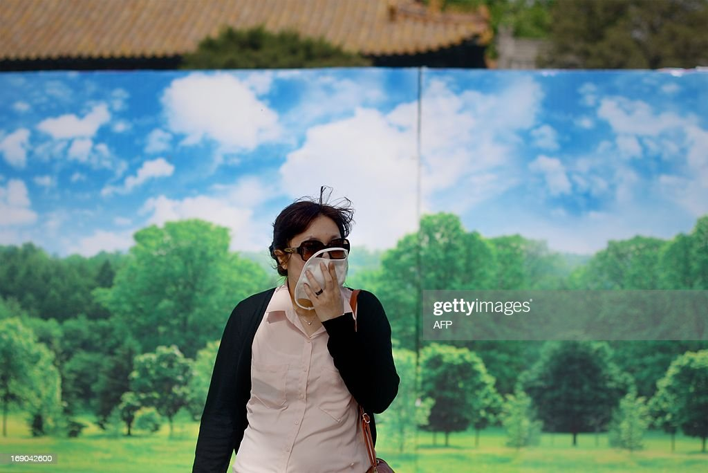 A woman covers her face as she walks past a billboard at the Forbidden City in Beijing on May 19, 2013. China will more than double the number of cities covered by air quality monitoring, as part of efforts to tackle heavy smog that has sparked huge public anger. Swathes of acrid haze have repeatedly shrouded large parts of the country in recent months, provoking outrage among Internet users and unusual outspoken calls for action, in the state-run media. AFP PHOTO / WANG ZHAO