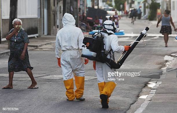 A woman covers her face walking past health workers fumigating in an attempt to eradicate the mosquito which transmits the Zika virus on January 28...