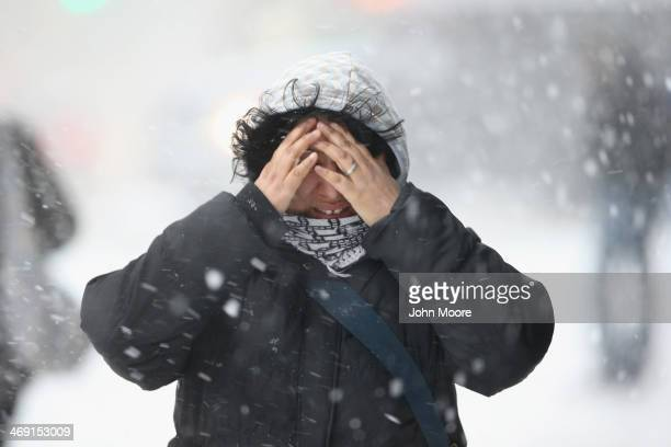 A woman covers her face while walking through the snow on February 13 2014 in New York City Heavy snow and high winds made for a hard commute morning...